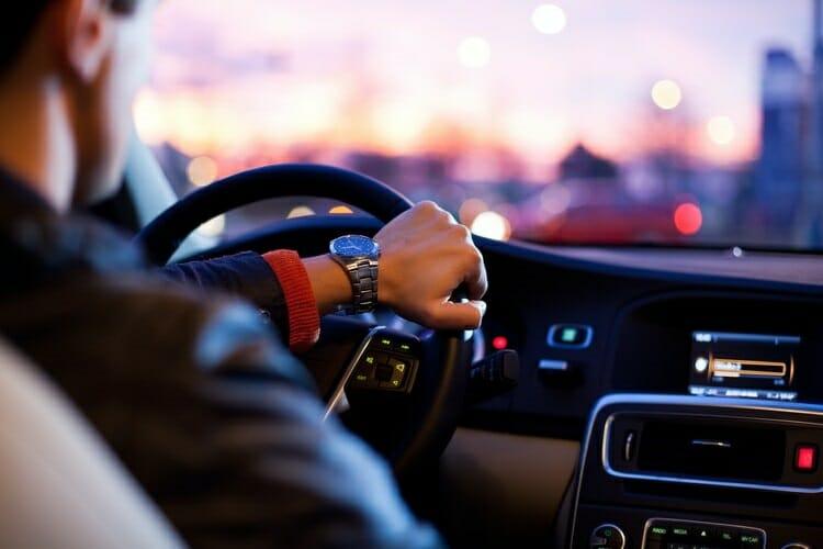 Como chegar no Paraguai com aplicativo de transporte, na parte interna de um carro, onde aparece o painel do veículo e mão do motorista no volante.