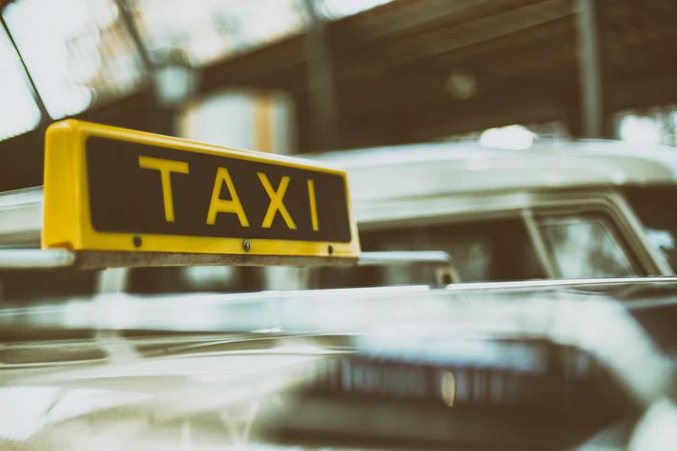 Parte de cima de um táxi, onde aparece uma plaquinha amarela, escrito 'Táxi'.