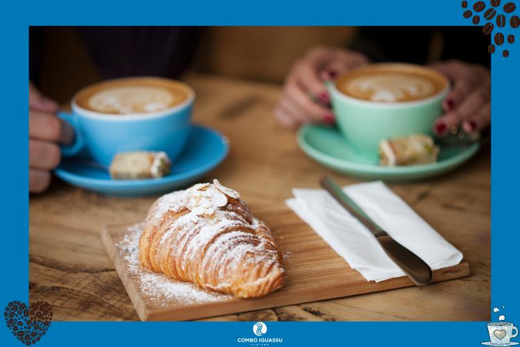 Duas pessoas tomando um café com um croissant em frente | Cafés em Foz do Iguaçu? Nós te indicamos alguns!