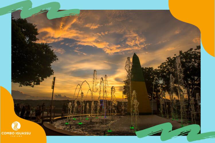 Visão linda do pôr do sol junto com o obelisco e chafarizes no Marco das Três Fronteiras.